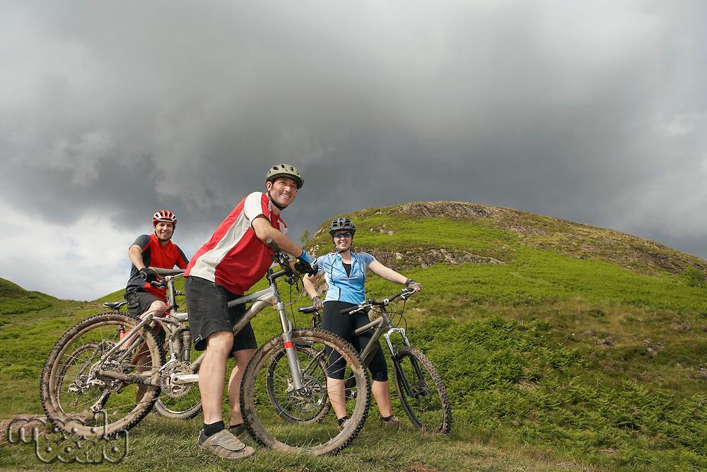 Three cyclists on hillside portrait