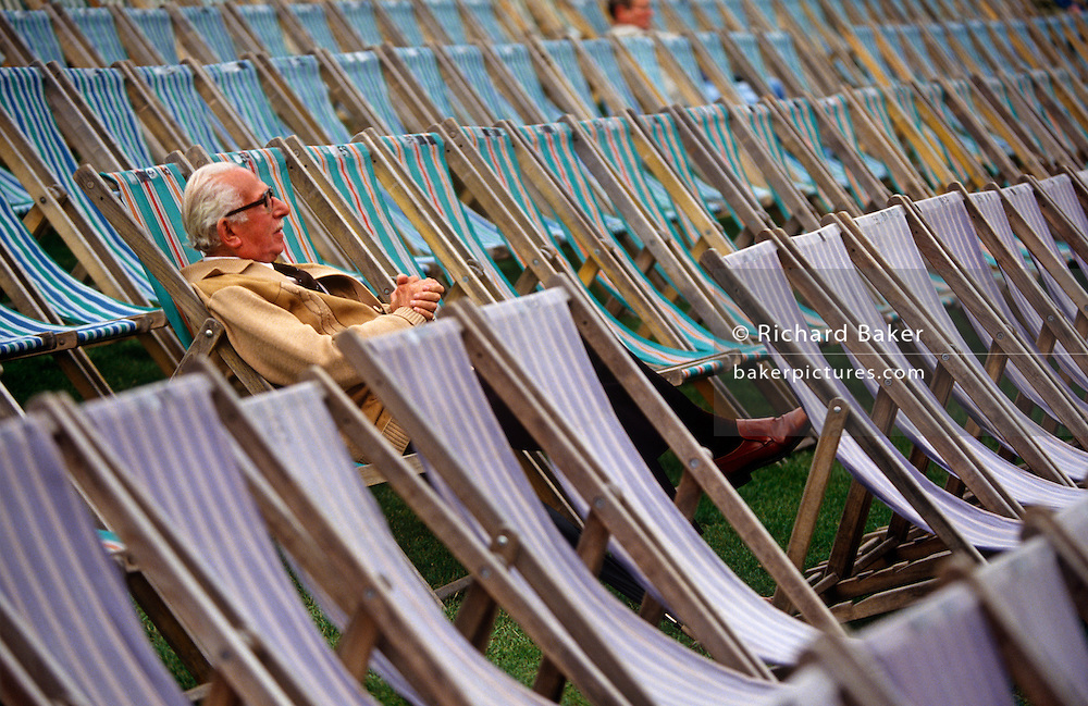 A lone pensioner sits in one deckchair among many before an outside concert at at Kenwood House, North London. Set in leafy grounds beside Hampstead Heath, these grounds  were remodelled by Robert Adam between 1764 and 1779. English Heritage host Summer concerts here and families and music fans spend war summer evenings listening to opera, classical or series of themed performances by visiting artists and groups. Here is also the source of one of London's lost rivers, The Fleet which rises here and flows downhill into the city where it becomes part of the sewer system, emerging in the Thames at Blackfriars. Extended caption ..