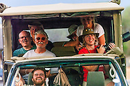 On safari in Kruger National Park, a group of happy photographers look on amused as I shoot their vehicle while walking backwards and nearly plowing over some unseen tourists on the road behind me. Much to their disappointment, I missed the tourists.