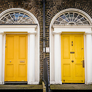 Two yellow iconic Dublin Georgian Doors against a brown bricked fascade of a georgian building