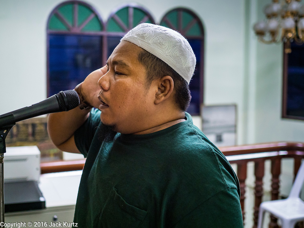 05 JUNE 2016 - BANGKOK, THAILAND: The muezzin does the call to prayer at Masjid Darul Faha, a small mosque in the Muslim majority neighborhood of Ban Krua in Bangkok on the night before the start of Ramadan. Ramadan is the ninth month of the Islamic calendar, and starts on June 6 this year. It is observed by Muslims worldwide as a month of fasting to commemorate the first revelation of the Quran to Muhammad according to Islamic belief. This annual observance is regarded as one of the Five Pillars of Islam. Islam is the second largest religion in Thailand.       PHOTO BY JACK KURTZ