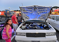 Bellmore, New York, USA. 7th August 2015. A young girl and others look at white 1987 Chevy Monte Carlo, owned by John Gilson, of Islip, with blue lights under raised hood, at the Friday Night Car Show held at the Bellmore Long Island Railroad Station Parking Lot. Gilson was one of many members of the South Side Boys auto club attending the Cruise Night. Hundreds of classic, antique, and custom cars were on view at the free weekly show, sponsored by the Chamber of Commerce of the Bellmores.