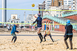 © Licensed to London News Pictures. 21/03/2020. Brighton, UK. Members of the Brighton Beach Volleyball Club play a game on the beach court as sunny weather is hitting the seaside resort. Photo credit: Hugo Michiels/LNP