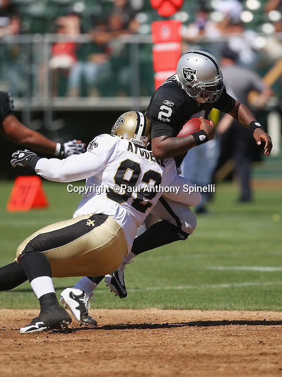 Oakland Raiders quarterback JaMarcus Russell (2) gets chased from the pocket and tackled by New Orleans Saints defensive tackle Remi Ayodele (92) during an NFL preseason football game, Saturday, August 29, 2009 in Oakland, California. The Saints won the game 45-7. ©Paul Anthony Spinelli