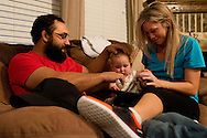 Johny Hendricks and his wife Christina play with their eight-month-old daughter, Avin, at their home in Midlothian, Texas on February 27, 2014.