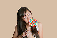 Portrait of beautiful young woman biting lollipop over colored background