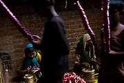 Children are decorating glass bracelets inside a house transformed into a small-scale workshop in the slum surrounding Firozabad, renowned as the 'glass city', in  Uttar Pradesh, northern India. Due to extreme poverty, over 20.000 young children are employed to complete the bracelets produced in the industrial units. This area is considered to be one of the highest concentrations of child labour on the planet. Forced to work to support their disadvantaged families, children as young as five are paid between 30-40 Indian Rupees (approx. 0.50 EUR) for eight or more hours of work daily. Most of these children are not able to receive an education and are easily prey of the labour-poverty cycle which has already enslaved their families to a life of exploitation. Children have to sit in crouched positions, use solvents, glues, kerosene and various other dangerous materials while breathing toxic fumes and spending most time of the day in dark, harmful environments. As for India's Child Labour Act of 1986, children under 14 are banned from working in industries deemed 'hazardous' but the rules are widely flouted, and prosecutions, when they happen at all, get bogged down in courts for lengthy periods. A ban on child labour without creating alternative opportunities for the local population is the central problem to the Indian Government's approach to the social issue affecting over 50 million children nationwide.