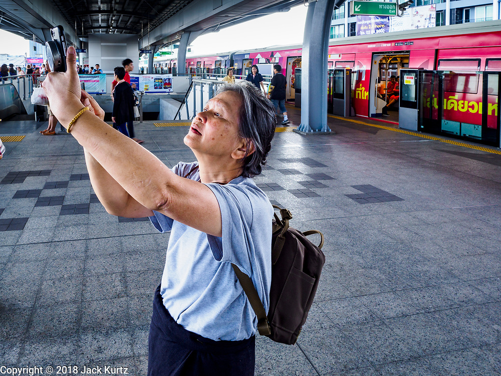 06 DECEMBER 2018 - SAMUT PRAKAN, THAILAND:  A woman photographs the Samrong station on the newly opened expansion of the BTS Skytrain. The 12.6 kilometer (7.8 miles) east extension of the Sukhumvit Line of the Bangkok BTS Skytrain goes into Samut Prakan, a town east of Bangkok.  The system is now 51 kilometers long (32 miles), including the 12.6 kilometer extension that opened December 06. About 900,000 people per day use the BTS.     PHOTO BY JACK KURTZ