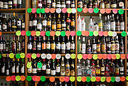 Bottles of wine and spirits stacked on a shelf, awaiting sale in a London off-license. .The term off-License applies to the licence granted to establishments allowing them to sell alcoholic beverages for consumption off the premises. The term derived from public houses, pubs, which possessed an off licence as part of their regular licence, allowing them to sell sealed alcoholic drinks (e.g., unopened bottles of wine) for consumption elsewhere.