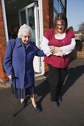 Carer helping old lady walking.
