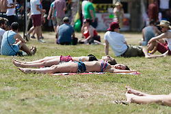 © Licensed to London News Pictures. 13/06/2014. Isle of Wight, UK.  Festival goers sunbathe in bikini tops and shorts in the hot morning sun at the Isle of Wight Festival 2014.   Today is expected to be the hottest day of the year.  The Isle of Wight festival is an annual music festival that takes place on the Isle of Wight. Photo credit : Richard Isaac/LNP