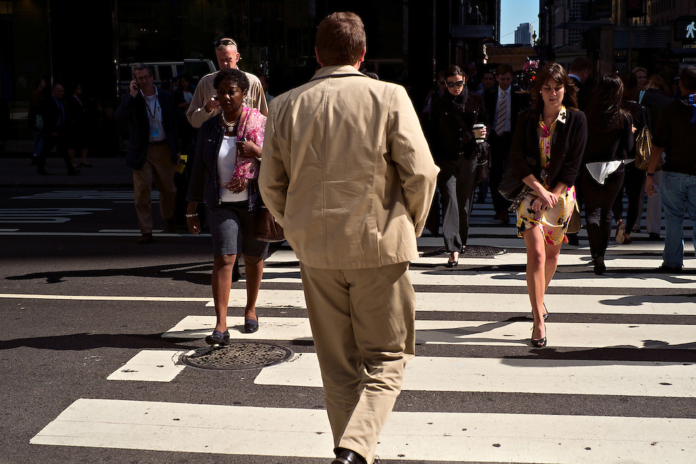 Man in beige suit crossing street