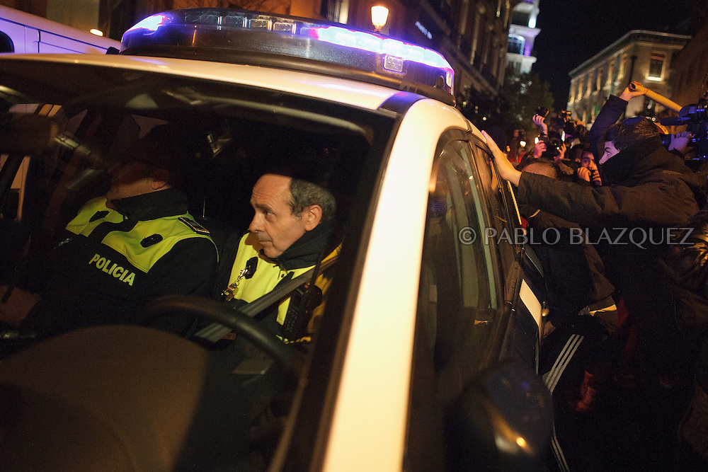 Protesters hit and push a police car after 'Surrounding the Congress' protest at Atocha Street on December 14, 2013 in Madrid, Spain. Social movements groups called a 'Rodea el Congreso' 'Surrounding the Parliament' protest in reaction to the financial and social cuts, but also a new law the Spanish government is working that aims to set heavy fines. Around 1,500 policemen were on duty to protect the congress. The bill will set up fines of up to 30,000 euros for offenses related to social movements protests, insulting the state or offending or filming the authorities. After the demonstration some protesters clashed with riot policemen