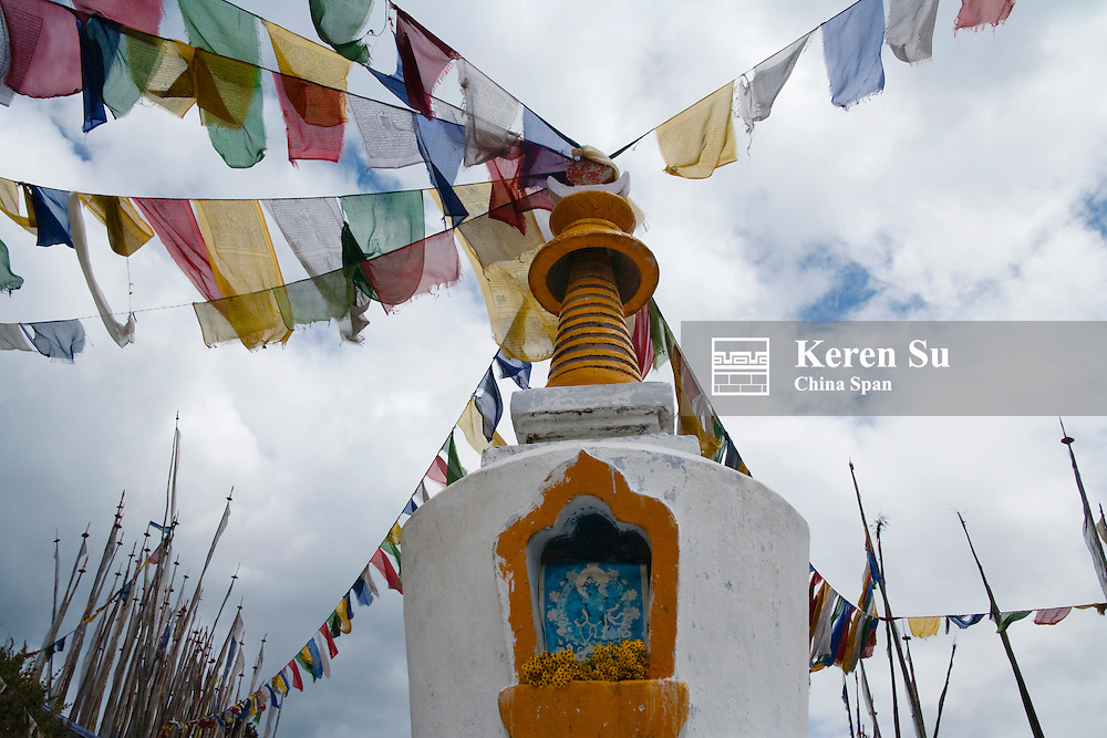 Praying flag poles with chorten in the mountain, Yotongla Pass, Bumthang area, Bhutan