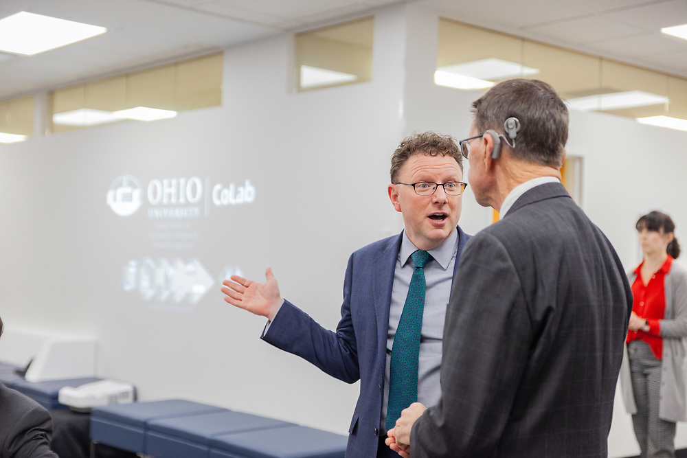 Matthew Shaftel, dean of the College of Fine Arts, and Cary Cooper, Board of Trustees member, talk at the grand opening and ribbon cutting for the new CoLab, October 18, 2018. (Photo by Stephen Zenner/Ohio University Libraries)