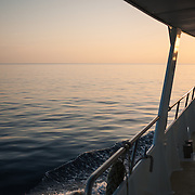 Very calm seas at sunset on the Great Barrier Reef. At right of frame is part of the MV Night Crossing, a charter fishing vessel based in Gladstone, Queensland, that takes groups on week-long trips out to the Swains Reef on the southern end of the Great Barrier Reef.