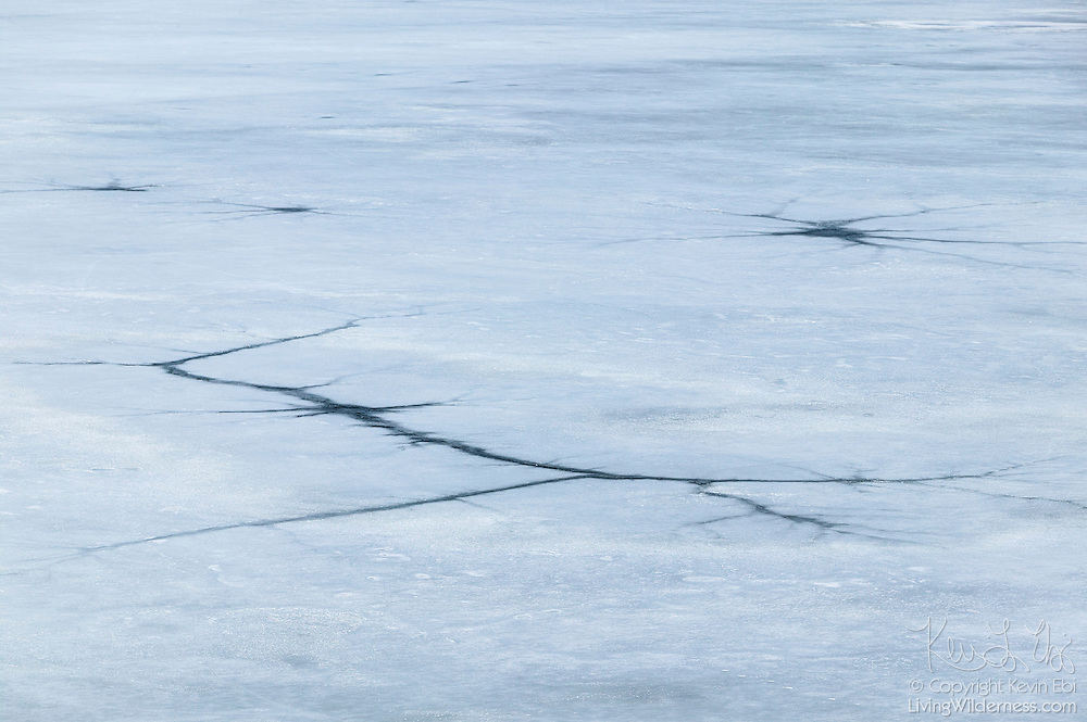 Several large cracks, some caused by rocks tumbling from the steep, rocky walls that surround the lake, are visible in the ice on Lake Crowley, located near Mammoth Lakes in Mono County, California.