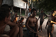 Boys from Kbal Romeas gather at sunset to enjoy some home-made rice wine, a highly alcoholic drink young villagers use to brew and sell. In the background, one of the many houses that have been sprayed in red paint with the writing LSS2 by the company carrying out the relocation project.
