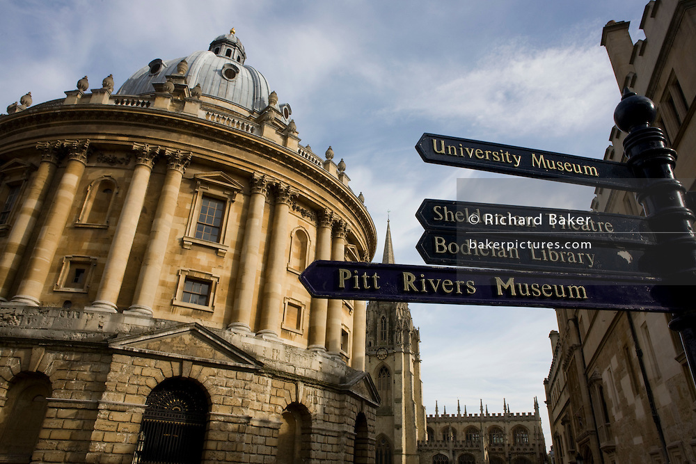 The Radcliffe Camera and tourist direction signs pointing to other famous Oxford landmarks
