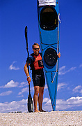 SEA KAYAKING, MAINE, paddler portrait w/ boat Marc Burgoin,