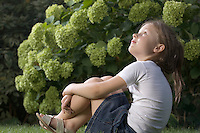 Young girl sits looking up from back garden