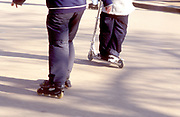 Two boys in the park, one on rollerblades, one on a mini scooter, UK 2004