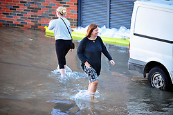 © Licensed to London News Pictures. 09/10/2016<br /> Townhall Square residents walking in flood water.<br /> Crayford town centre in Kent is closed and flooded this morning with hundred of homes across Dartford,Wilmington,Bexley,Crayford,Stone without water because of an over night issue with repairs by Thames Water at Crayford Road,Crayford.    Residents at Townhall Square have been flood with the under ground car park full of water. <br /> <br /> Photo credit :Grant Falvey/LNP