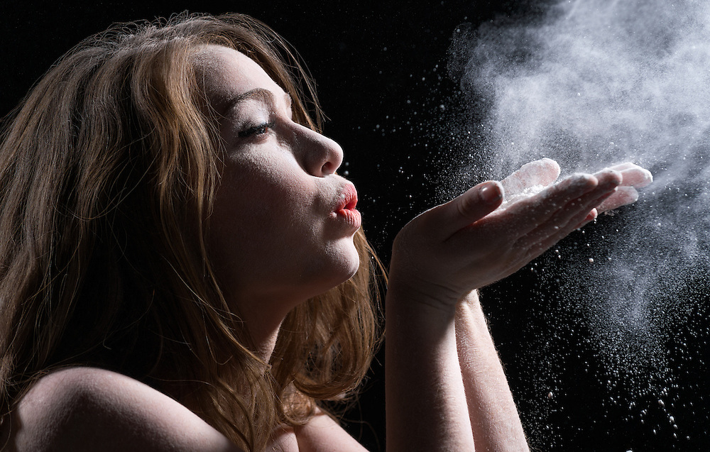 Portrait of young woman blowing powder from hands
