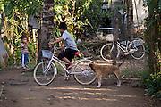 Een jongetje fietst bij zijn huis in Phnom Penh