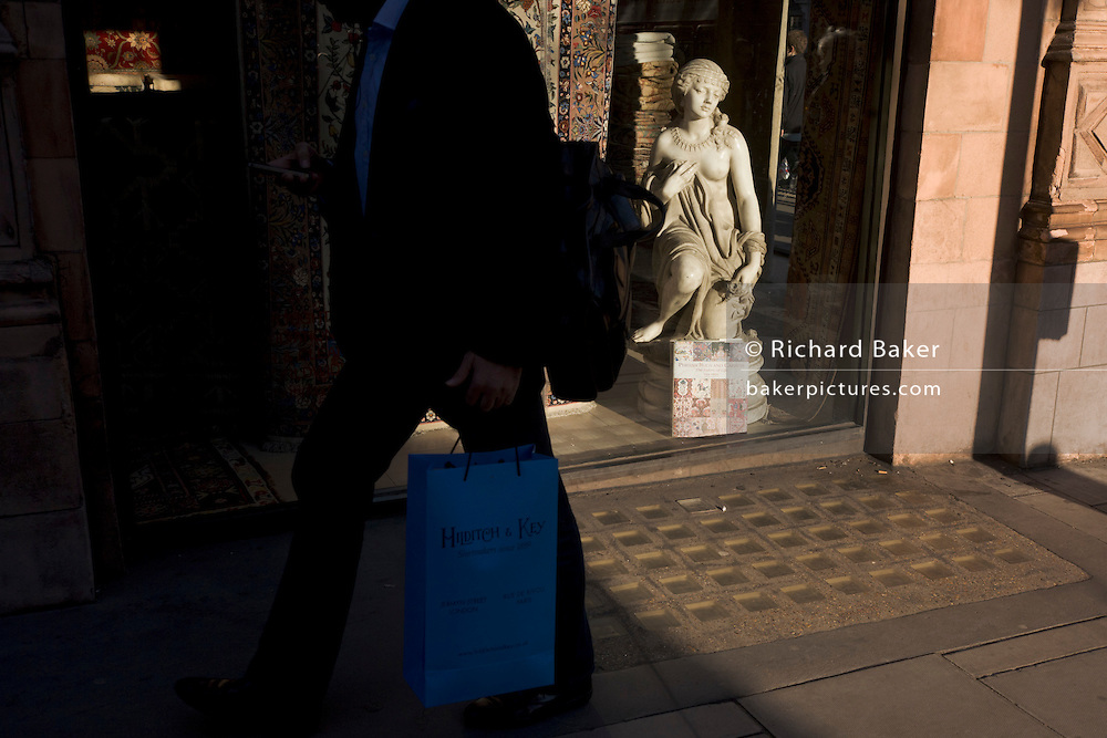 Man carries blue shopping bag past small girl statue credited to the 19th century Florence-born artist Raffaello Romanelli.