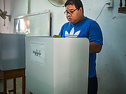 08 NOVEMBER 2015 - YANGON, MYANMAR: A man in a voting booth marks his ballot at his voting place in a public school in central Yangon. The citizens of Myanmar went to the polls Sunday to vote in the most democratic elections since 1990. The National League for Democracy, (NLD) the party of Aung San Suu Kyi is widely expected to get the most votes in the election, but it is not certain if they will get enough votes to secure an outright victory. The polls opened at 6AM. In Yangon, some voters started lining up at 4AM and lines were reported to long in many polling stations in Myanmar's largest city.      PHOTO BY JACK KURTZ