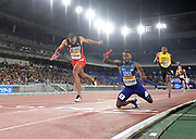 May 12, 2019; Yokohama, JPN; Machel Cedenio (TTO) and  Paul Dedewo (USA) lean at the finish line in the 4 x 400m relay during the IAAF World Relays at International Stadium. Trinidad & Tobago won in 3:01.81. The United States was disqualified.