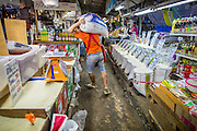 "03 OCTOBER 2012 - BANGKOK, THAILAND:   A porter carries a sack of rice on his shoulders in Khlong Toey Market. Khlong Toey (also called Khlong Toei) Market is one of the largest ""wet markets"" in Thailand. Thousands of people shop in the sprawling market for fresh fruits and vegetables as well meat, fish and poultry every day.     PHOTO BY JACK KURTZ"