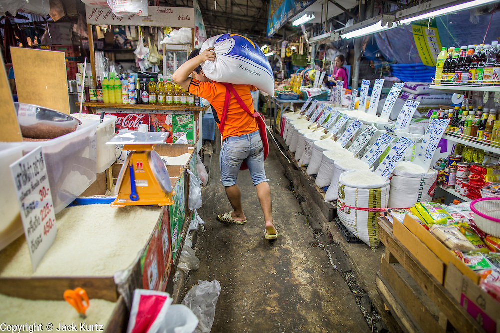 """03 OCTOBER 2012 - BANGKOK, THAILAND:   A porter carries a sack of rice on his shoulders in Khlong Toey Market. Khlong Toey (also called Khlong Toei) Market is one of the largest """"wet markets"""" in Thailand. Thousands of people shop in the sprawling market for fresh fruits and vegetables as well meat, fish and poultry every day.     PHOTO BY JACK KURTZ"""