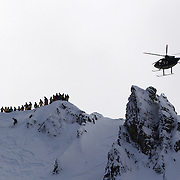 Competitors on top of Mount Albert during competition as a helicopter flies past during the World Heli Challenge Extreme Day at Mount Albert on Minaret Station, Wanaka, New Zealand. 1st August 2011