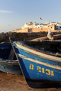The front part of a blue fishing boat and the city Essaouira in the background. Morocco. Africa.