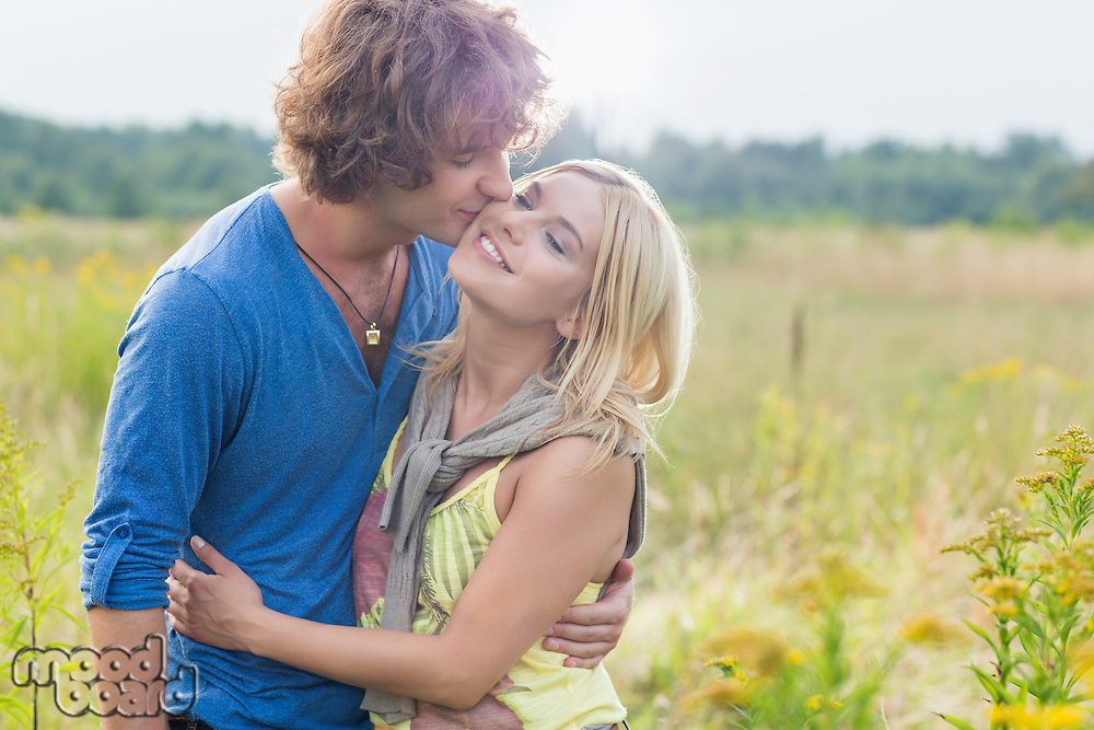 Romantic young man kissing woman in field