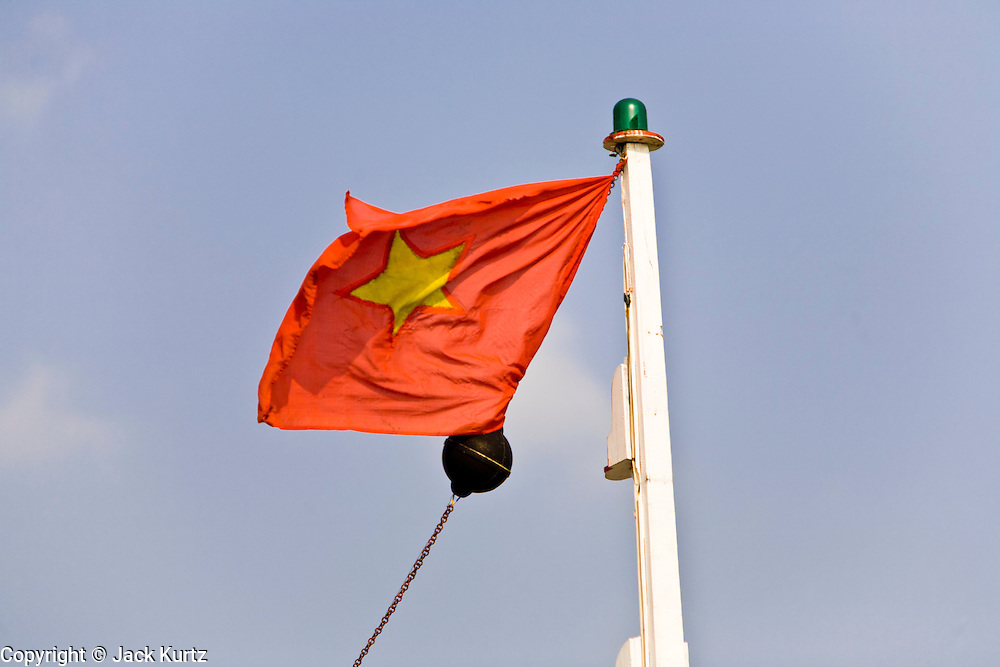 11 MARCH 2006 - CAI BE, TIEN GIANG, VIETNAM: A Vietnamese flag flies from the mast of a ship in the Mekong River delta. The Mekong is the lifeblood of southern Vietnam. It is the country's rice bowl and has enabled Vietnam to become the second leading rice exporting country in the world (after Thailand). The Mekong delta also carries commercial and passenger traffic throughout the region.  Photo by Jack Kurtz