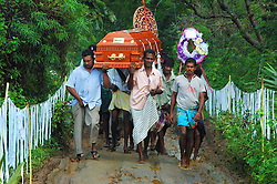 Sri Lanka, Kurunegala, 2006. Family members bear their mother's coffin down a spirit path marked with white cloth. Firecerackers were thrown to scare ghosts before the burial.