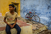 A boy sits at the entrance to his home, while his bike stands against the blue wall. In the old part of Bundi, houses are painted in vivd colors.