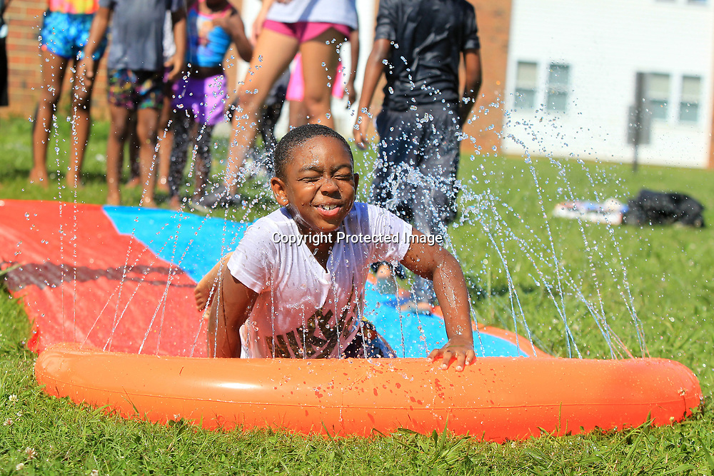 Tramontae Gill, 7, of Tupelo, breaks through the water after he rides down the slide during soccer camp at Hilldale Apartments in Tupelo on Wednesday morining. The children rotated from playing soccer and the water slide before as part of the morning schedule.