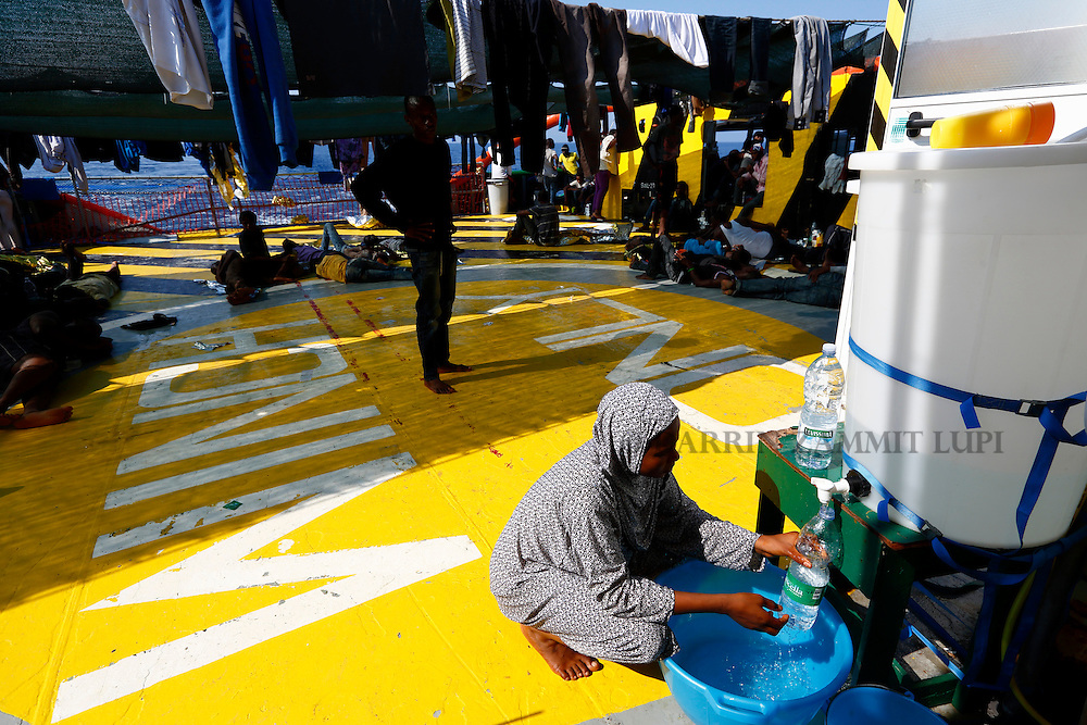 A migrant fills a bottle with water on the deck of the Medecins san Frontiere (MSF) rescue ship Bourbon Argos somewhere between Libya and Sicily August 8, 2015.  Some 241 mostly West African migrants on the ship are expected to arrive on the Italian island of Sicily on Sunday morning, according to MSF.<br /> REUTERS/Darrin Zammit Lupi <br /> MALTA OUT. NO COMMERCIAL OR EDITORIAL SALES IN MALTA