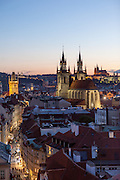 """View to the Prague cityscape and """"Celetna street"""" and the towers of Tyn Church located at Old Town Square. On the right Prague Castle and St. Vitus Cathedral during sundown."""