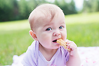 Baby eating biscuit outdoors at picnic
