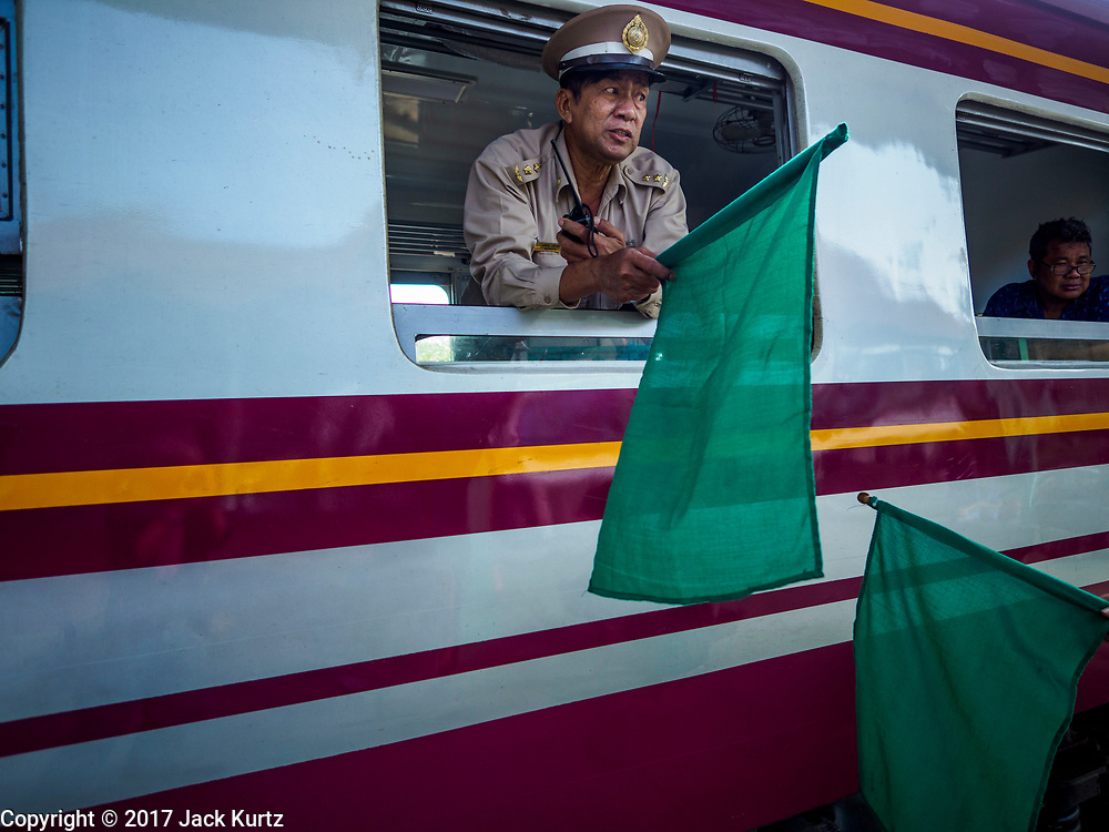 31 MAY 2017 - CHACHOENGSAO, THAILAND: A conductor waves a green flag as a Bangkok bound train leaves the train station in Chachoengsao, a provincial town about 50 miles and about an hour by train from Bangkok. The train from Chachoengsao to Bangkok takes a little over an hour but traffic on the roads is so bad that the same drive can take two to three hours. Thousands of Thais live outside of Bangkok and commute into the city for work on trains, busses and boats.       PHOTO BY JACK KURTZ