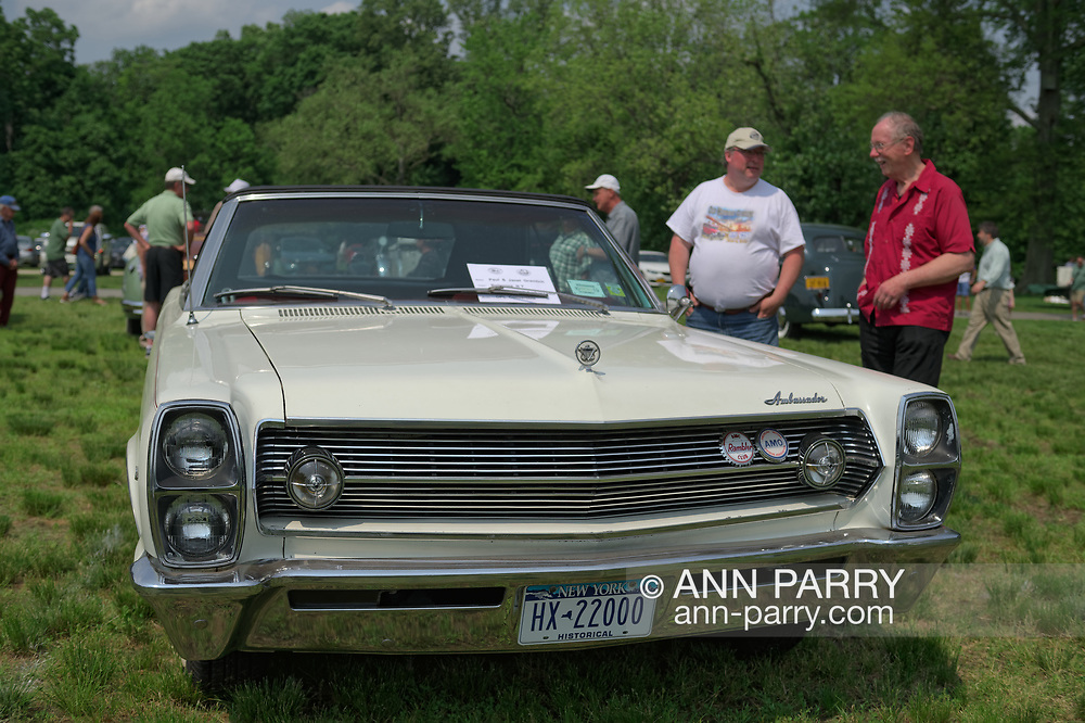 Old Westbury, New York, USA. June 2, 2019. L-R, KEITH GRAMLICH, of East Meadow, and BOB STUHMER, of Garden City Park, chat as they look at the white 1967 AMC Ambassador, DPL trim convertible, owned by Keith's parent, Paul & Janet Gramlich, os Bellerose, at the 53rd Annual Spring Meet Antique Car Show, sponsored by the Greater NY Region (NYGR) of the Antique Automobile Club of America (AACA), at Old Westbury Gardens, a Long Island Gold Coast estate.