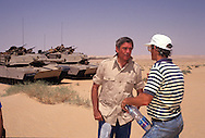 Dan Rather talks to his producer on a story on US troops in the desert.  Note:  actually we were taking a small lunch break eating  the MRE's while Rather's cameraman was getting very sick--he recovered and was able to work.  The tanks in the background are M 1 A 1.  There was a herd of camels near by and  the tanks went near the camel herd which produced a scene of tanks and  camels.  This footage was classic and used thousnds of times to illustrate stories on the Gulf War.  It was used by all the networks and especially CNN because everything was pooled...Photograph by Dennis Brack, BB 29