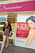 A young woman coming out of a self tanning salon, Brighton 2009
