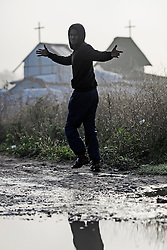 © Licensed to London News Pictures. 23/10/2016. Calais, France. A young migrant man gestures to the camera as he walks in front of the church at the camp, act sunrise. Daily life continues as preparations begin for the demolition of the migrant camp in Calais, France, known as the 'Jungle'. French authorities have given an eviction order to thousands of refugees and migrants living at the makeshift living area of the French coast. Photo credit: Ben Cawthra/LNP