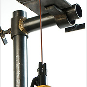 Position of the electrode and electrode holder when welding in the overhead for position travel toward the welder.<br /> <br /> Shielded metal arc welding (SMAW), or informally as stick welding, is a manual arc welding process that uses a consumable electrode coated in flux to lay the weld. An electric current, in the form of either alternating current or direct current from a welding power supply, is used to form an electric arc between the electrode and the metals to be joined.